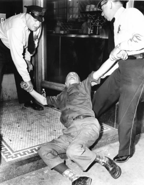 "Chicago Police officers Stephen Schumack, left, and Louis Krotz, right, remove a skid row ""downer"" on Madison Street, circa July 1954. A Tribune photographer followed Schumack and Krotz, who's job is to pick up drunks on skid row eight hours a day. Madison Street was the heart of the cheap wine and flophouse district. After one of the drunks became sick on Officer Krotz, he commented, ""A shirt a day on this job."""