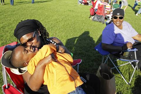 Kendra Finley, left, kisses her son Elijah Boone, 6, while Shawn Finley, right, watches.