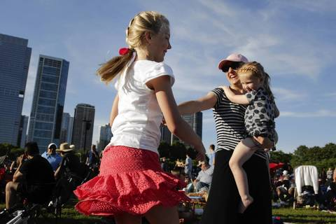 Victoria Andrews of Madison, Wis., holds her daughter Skye, 3, and dances with her daughter Tyne, 10, while they and dad listen to music.