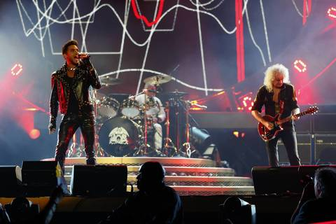 Queen's Brian May, right, and Roger Taylor, center, perform with Adam Lambert, left, at United Center in Chicago.