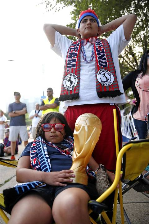 Amaris Lemos, 9, and her brother Roberto, 14, watch the second half of the USa-Portugal match.