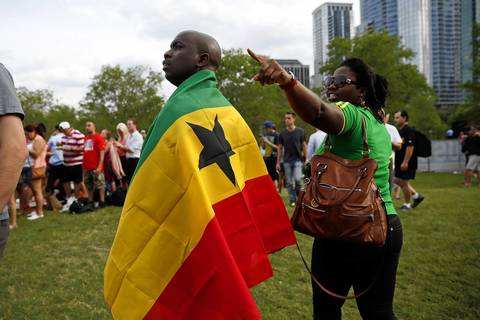 Ghana fans Ervay Oyenen and Francesca Bedzra watch their country's World Cup match against the United States on a video screen in Grant Park.