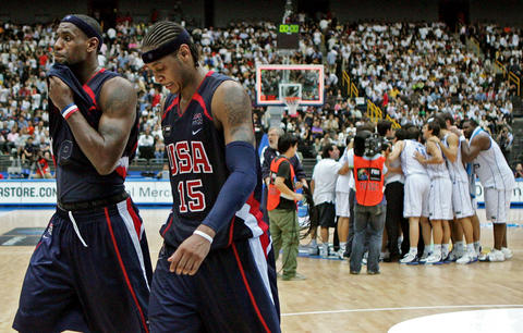 U.S. players LeBron James and Carmelo Anthony leave the court while Greek players celebrate their victory in the semifinals of the World Basketball Championship.