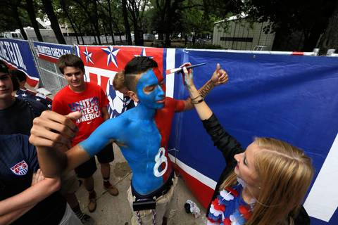 A World Cup fan gets a final touch-up before heading into Grant Park in Chicago to watch the U.S. match against Germany.