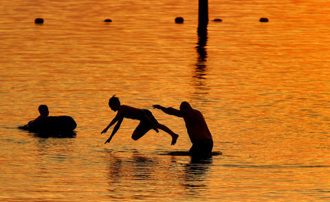 Staff Photo Of The Week: June 14-June 20, 2014     Shawn Allen, right, throws his eleven-year-old son, Josh, into the water as brother Chris watches as the sun sets at Huntington Beach Tuesday evening. No Mags, No Sales, No Internet, No TV