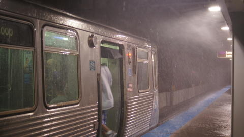 A commuter dodges the rain to board a train at the CTA's Fullerton stop.