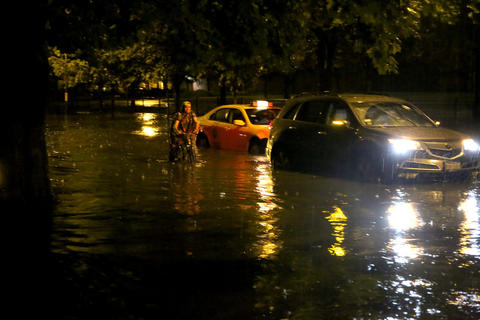 A bicyclist rides by a flooded-out car and a taxi which made it through the high waters in the Lakeview neighborhood of Chicago.