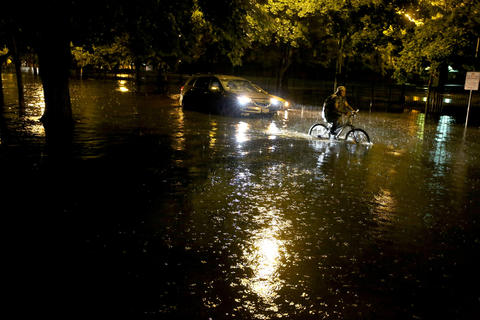 A bicyclist rides by a flooded-out car in the Lakeview neighborhood of Chicago.