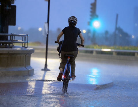 A cyclist on Roosevelt Road in Chicago is caught in a downpour on Monday.