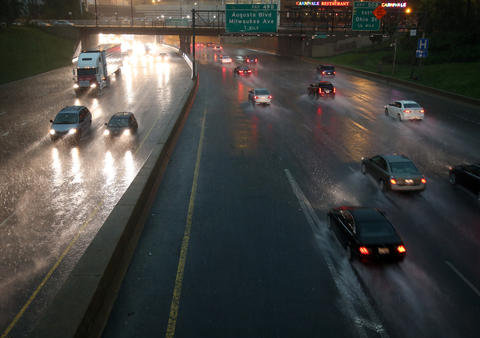 Traffic on the Kennedy Expressway at Lake Street in Chicago lifts a spray into the air during a downpour on Monday.