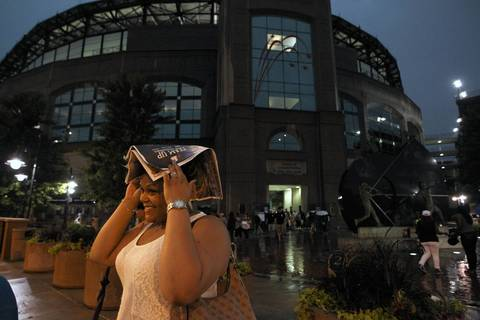 Krystina Perkins uses a newspaper to keep the rain away after at U.S. Cellular Field, following the cancellation of the game between the White Sox, and the Los Angeles Angels. Perkins was very disappointed since this would have been her first White Sox game ever.