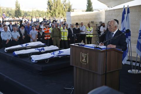 Israeli President Shimon Peres (R) eulogizes the three Israeli teens who were abducted and killed in the occupied West Bank, Gil-Ad Shaer, U.S.-Israeli national Naftali Fraenkel, both 16, and Eyal Yifrah, 19, during their joint funeral in the Israeli city of Modi'in July 1, 2014. Tens of thousands of mourners joined in an outpouring of national grief on Tuesday at the burial of the three Israeli teenagers whose kidnapping and killing Israel blamed on the Palestinian Islamist group Hamas. The Islamist group has neither confirmed nor denied involvement in the disappearance of the students as they hitchhiked near a Jewish settlement on June 12 nor in the cross-border rocket salvoes from Gaza.