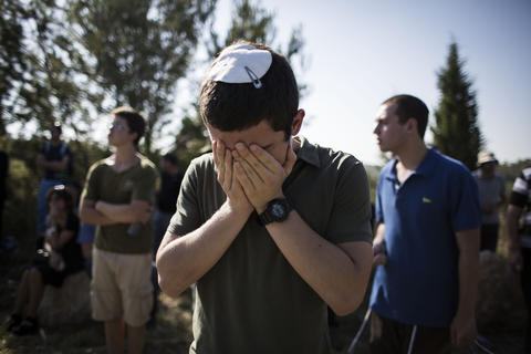 People pray during the funeral ceremony held for the three Israeli teenagers found dead, on July 1, 2014 in Modiin, Israel. The bodies of Eyal Yifrah, 19, Gilad Shaar, 16, and Naftali Fraenkel, 16, were found on Monday, north of the Palestinian town Halhul, near Hebron. The teenagers were reported missing since June 12.
