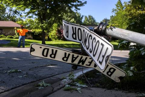 Damaged street signs lie along Flossmoor Road where village crews are removing downed trees.