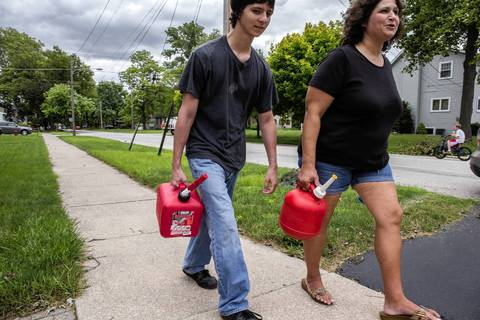 Sandy Hernandez and her son Dean, 19, carry gasoline for their generators as ComEd crews continue to restore power after storm damage in Midlothian.