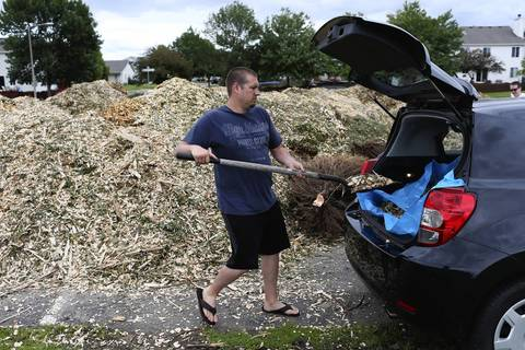 Dan Kelly loads his car with free mulch from downed trees after Monday's tornado in Lakewood Falls, a subdivision of Romeoville.
