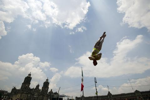 Circus workers perform as they take part in a protest against a law which prohibits the use of animals in their shows at Zocalo Square in Mexico City on July 02, 2014. The law was approved Monday by the local assembly of Mexico City.