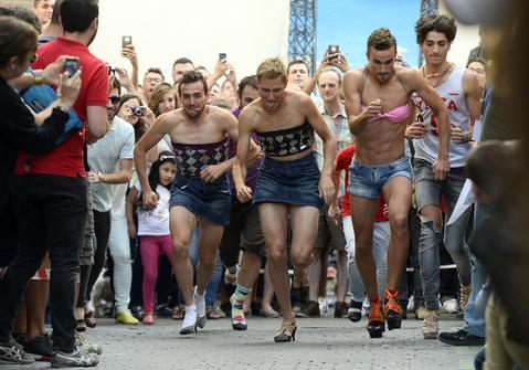 Participants run during a high-heel race at a Gay Pride party in the central neighborhood of Chueca in Madrid on July 3, 2014.