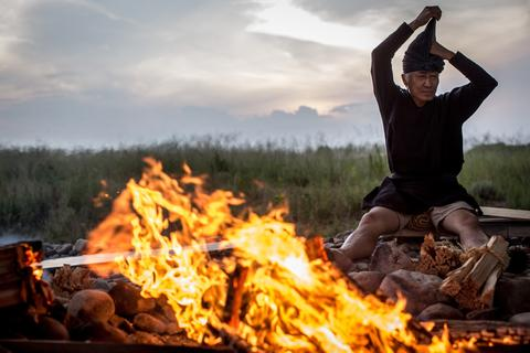Cormorant master, Mr. Masahiko Sugiyama puts on his traditional Kazori-Eboshi (hat) around a bonfire prior to the start of the nights Ukai on July 2, 2014 in Gifu, Japan.