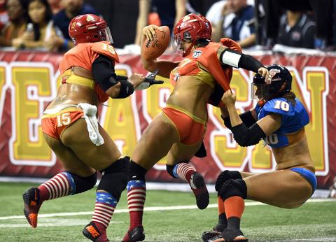 Quarterback Sindy Cummings #7 of the Las Vegas Sin is tackled by Kim Perez #10 of the Chicago Bliss as Elise Barkman #15 of the Sin moves in during their game at the Thomas & Mack Center on July 3, 2014 in Las Vegas, Nevada. Chicago won 27-18.