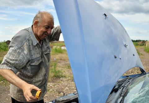 A driver of a car examines the engine with the hood pierced by shrapnel at a Ukrainian forces check-point near Slavyansk.