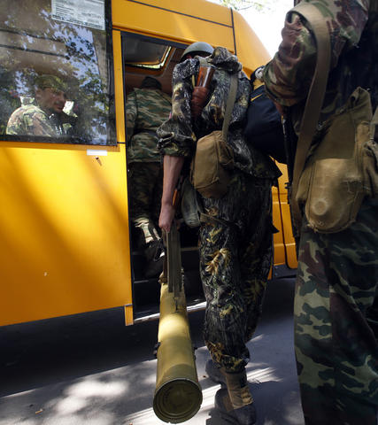 Armed pro-Russian separatists board the bus as they leave their positions in Kramatorsk in eastern Ukraine.