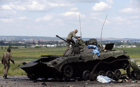 Ukrainian soldiers check a destroyed armored vehicle at Slaviansk in eastern Ukraine.