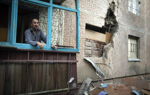 Valery, 63, looks out of a window of his apartment, which was damaged by shelling, in Slaviansk.