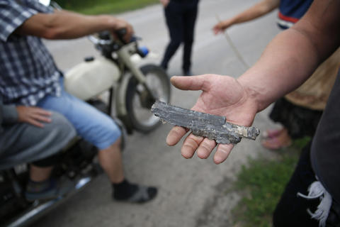 A local resident shows a fragment of a shell found after fighting near Slaviansk in eastern Ukraine.