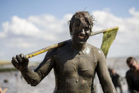"A participant smiles as he comes up with a flag after a handball match at the ""Wattoluempiade,"" or Mud Olympics, in the northern German city of Brunsbuettel, July 6, 2014. During the event, participants also join in other games including soccer and volleyball matches."