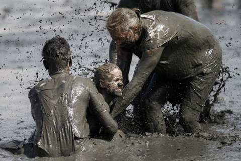 """Participants compete for the ball during a handball match at the """"Wattoluempiade,"""" or Mud Olympics, in the northern German city of Brunsbuettel, July 6, 2014. During the event, participants also join in other games including soccer and volleyball matches."""