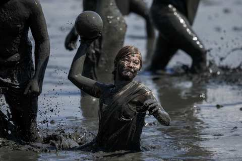"""A participant throws the ball during a handball match at the """"Wattoluempiade,"""" or Mud Olympics, in the northern German city of Brunsbuettel, July 6, 2014. During the event, participants also join in other games including soccer and volleyball matches."""