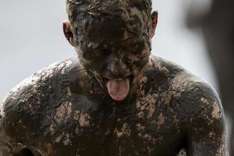 "A participant reacts during a soccer match at the ""Wattoluempiade,"" or Mud Olympics, in the northern German city of Brunsbuettel, July 6, 2014. During the event, participants also join in other games including handball and volleyball."