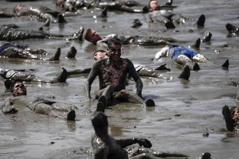 "A participant smiles as he takes part in an attempt to break the world record for total number of 'mud angels' at the ""Wattoluempiade,"" or Mud Olympics, in the northern German city of Brunsbuettel, July 6, 2014. During the event, participants also join in other games including football, handball and volleyball."