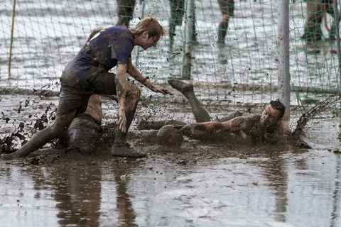 """Players fight for the ball during a soccer match at the """"Wattoluempiade,"""" or Mud Olympics, in the northern German city of Brunsbuettel, July 6, 2014. During the event, participants also join in other games including handball and volleyball."""