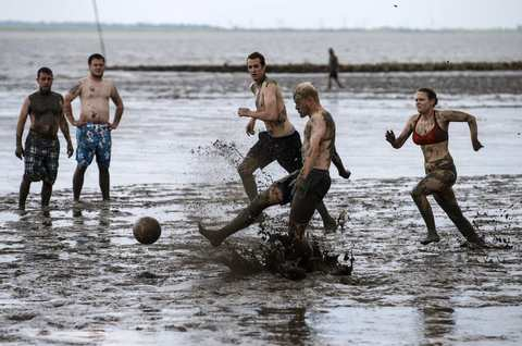 "Players fight for the ball during a soccer match at the ""Wattoluempiade,"" or Mud Olympics, in the northern German city of Brunsbuettel, July 6, 2014. During the event, participants also join in other games including handball and volleyball."
