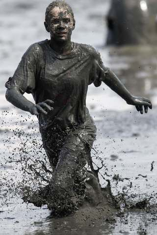"A participant runs for the ball during a handball match at the ""Wattoluempiade,"" or Mud Olympics, in the northern German city of Brunsbuettel, July 6, 2014. During the event, participants also join in other games including soccer and volleyball matches."