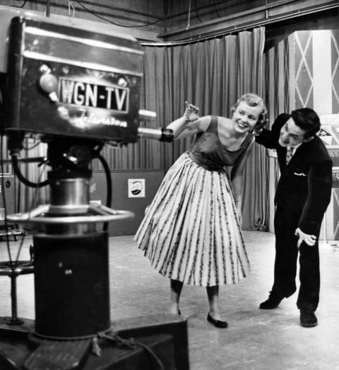 Carol Johnson of Austin High School and Bob Dipper of Evergreen Park High School take a quick look into the camera during WGN-TV's Bandstand Matinee on May 29, 1956. WGN and popular disc jockey Jim Lounsbury hosted the rock 'n' roll show for thousands of gyrating teenagers from 1954 to 1963.