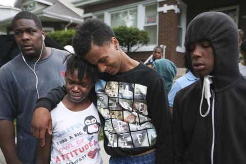 Deja Bates, 11, second from left, is comforted by Marca Parker after the death of her brother.