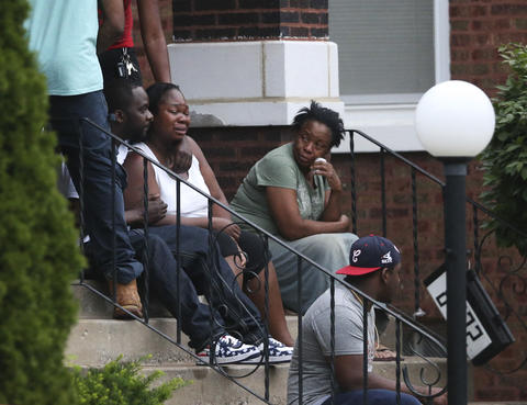 Georgina Utendhal, center, is held by her fiance Andre Holden, as she waits for details of her son's death.