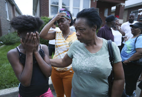 Georgia Utendhal, right, comforts one of her granddaughters, whose brother was allegedly shot and killed by a member of Chicago Police department.