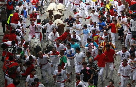 Runners sprint in front of Torrestrella fighting bulls at the entrance to the bullring during the first running of the bulls of the San Fermin festival in Pamplona July 7, 2014.