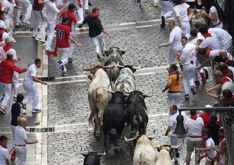 Participants run in front of Torrestrella's bulls during the first bull-run of the San Fermin Festival, on July 7, 2014, in Pamplona, northern Spain.