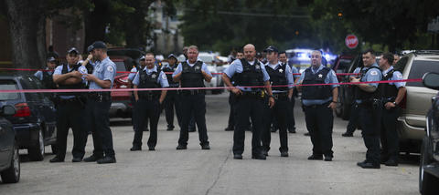 Chicago Police officers wait at the crime scene while a large crowd disperses at the 8700 block of S. Sangamon St.