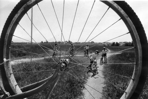 June 28, 1973: Bike trails and riders are visible through the spokes of a bicycle at a play area near the Little Cal in Glendale Heights.