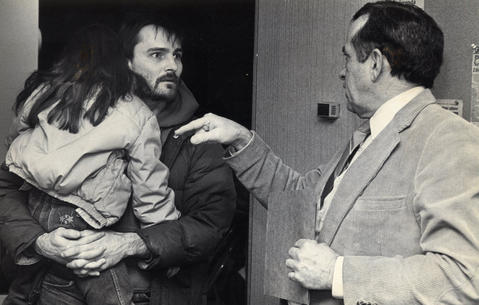 March 1, 1987: Tom Hall of the Environmental Protection Agency explains his findings to Walter Thomas, who holds daughter Jessica, 7, a student at Queen Bee School. Officials determined that asbestos found at the school was not a threat.