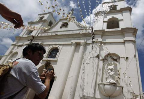 A man takes a picture of a damaged church of San Pedro, in the San Marcos region, in the northwest of Guatemala, July 7, 2014. A strong earthquake shook the border between Guatemala and Mexico on Monday, killing at least five people, including a newborn boy, damaging dozens of buildings and triggering landslides. Much of the damage from the 6.9-magnitude quake was reported in the Guatemalan border region of San Marcos, where it downed power lines, cracked buildings and triggered landslides which blocked roads.