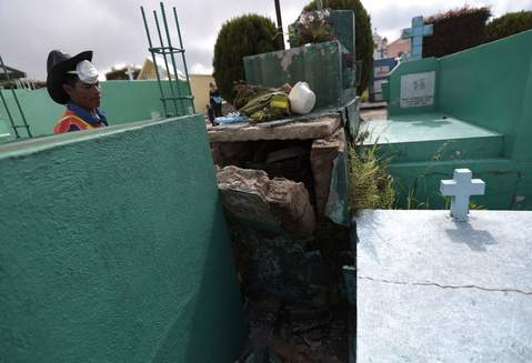 A cemetery employee stands next to a grave damaged by the earthquake in the cemetery of San Marcos, in the San Marcos region, in northwest Guatemala, July 7, 2014. A strong earthquake shook the border between Guatemala and Mexico on Monday, killing at least four people, including a newborn boy, damaging dozens of buildings and triggering landslides. The 6.9 magnitude quake struck near the frontier. Much of the damage was reported in the Guatemalan border region of San Marcos, where it downed power lines, cracked buildings and triggered landslides which blocked roads.