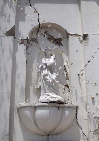 A damaged religious symbol is pictured in a damaged church of San Pedro, in the San Marcos region, in the northwest of Guatemala, July 7, 2014. A strong earthquake shook the border between Guatemala and Mexico on Monday, killing at least five people, including a newborn boy, damaging dozens of buildings and triggering landslides. Much of the damage from the 6.9-magnitude quake was reported in the Guatemalan border region of San Marcos, where it downed power lines, cracked buildings and triggered landslides which blocked roads.