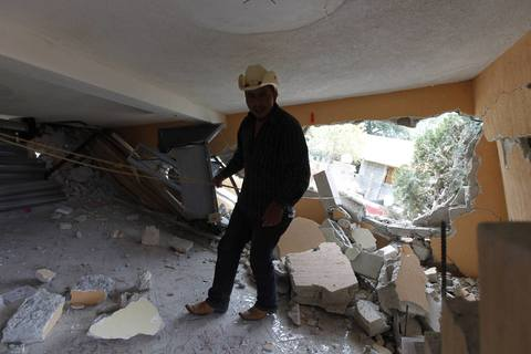 A man stands in an earthquake-damaged house in the San Marcos region, in the northwest of Guatemala, July 7, 2014. A strong earthquake shook the Guatemalan border with Mexico on Monday, killing at least four people, damaging dozens of buildings and triggering landslides. The 6.9 magnitude quake struck near the frontier, and much of the damage was reported in the Guatemalan border region of San Marcos, where it downed power lines, opened cracks in buildings and triggered landslides which blocked roads.